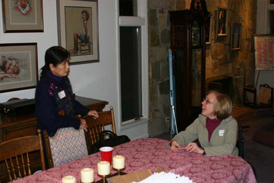 "Treasurer JoAnna Allen and Secretary Christa Bucks Camacho address newsletters at  the group's Christmas party at the Fittons in 2004.  Note the (in)famous ""Yearly Planning Board"" in the background right."
