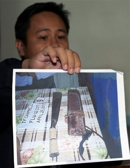 Philippine National Police Chief Inspector Rino Corpus displays a photo of the alleged weapon used by Juan Duntugan in digging a shallow grave to bury U.S. Peace Corps volunteer Julia Campbell