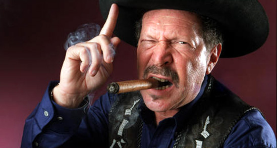 Humorist and gubernatorial candidate Kinky Friedman wandered around the University of Texas campus Wednesday, a walking cloud of cigar smoke that was part vaudeville, part news conference, part campaign stop