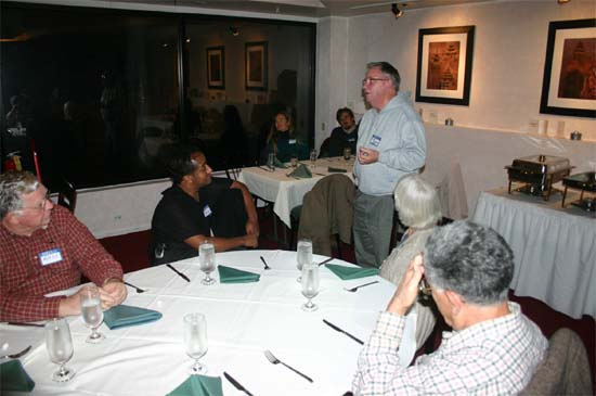 "Lee Tuveson from Nepal 1 speaks to the Maryland Returned Volunteers at the group's ethnic dinner at the Nepali ""Kathmandu Restaurant"" in 2004 as Russell Faust, Kay Muldoon-Ibrahim, and Kamal Ibrahim listen."