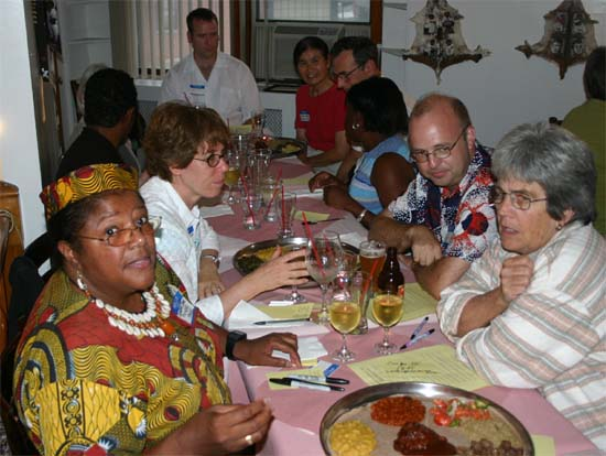 "Returned Volunteers meet at the group's ethnic dinner at the Ethiopian ""Dukem Restaurant"" in 2004. Tracey Feild, JoAnna and Ken Allen, and Charma Rhoden  enjoy an animated conversation at the meal. Tracey Feild organized this event that was one of our most successful ethnic dinners."