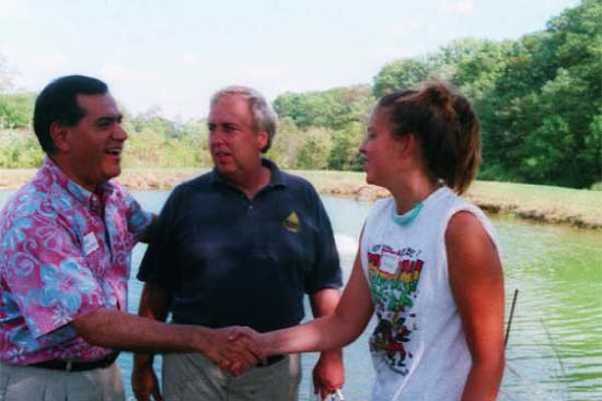 Peace Corps Director Gaddi Vasquez (left) spoke at the group's Picnic in 2002.  Here he is talking with the group's host for the picnic Tom Jacobs and his daughter Geneve.