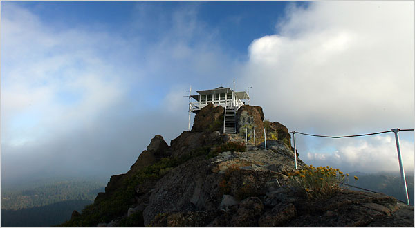 Liberia RPCV Michael Gates, a contract fire lookout with the U.S. Forest Service, spends his summers in a lookout tower that sits at 6700 feet atop Saddleback Mountain in the Tahoe National Forest near Downieville, Ca
